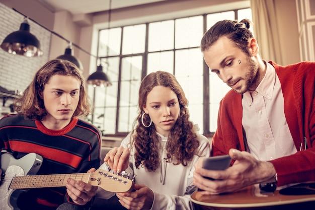 Покажите музыкальные ноты. талантливый опытный бородатый наставник по игре на гитаре держит телефон и показывает ноты