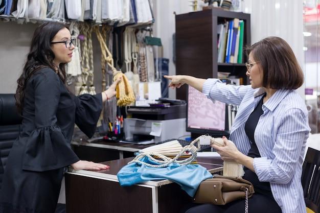 Show room interior female salesman showing fabrics