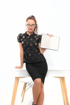 Покажи пример. элегантная женщина держать ноутбук, копировать пространство. предприниматель на рабочем месте. уверенная леди босс. девушка показать книгу. сексуальная студентка в классе. обратно в школу. учительница в очках.
