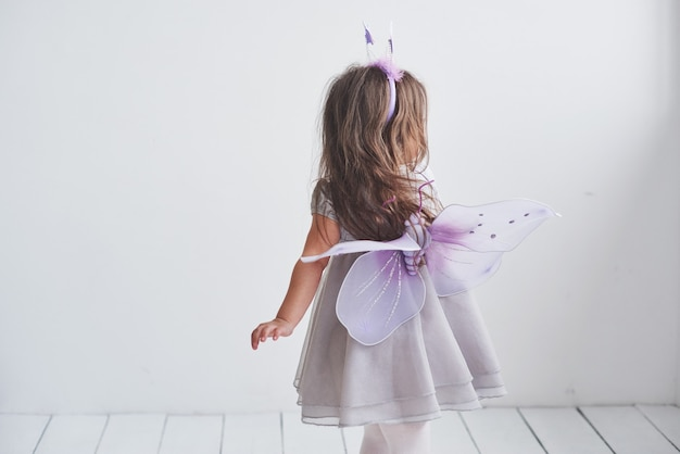 Show your wings. lovely little girl in the fairy costume standing in room.