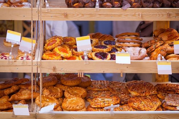 신선한 페이스트리가있는 빵집 쇼케이스 : 피자, 딸기와 양귀비 씨가 들어간 빵, 고기 파이
