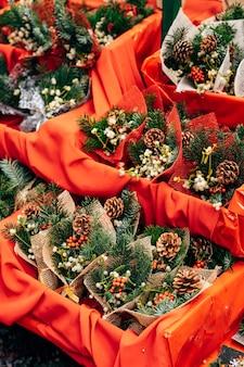 クリスマスツリーの枝のバンプベリーとヒイラギのクリスマスマーケットの封筒の束のショーケース