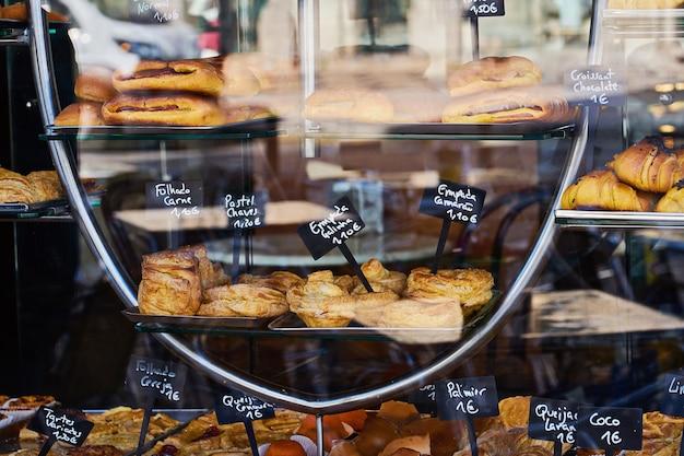 Витрина уютной пекарни с разнообразной выпечкой, печеньем и пирогами. надпись на португальском эклере, торт, шоколад, безе