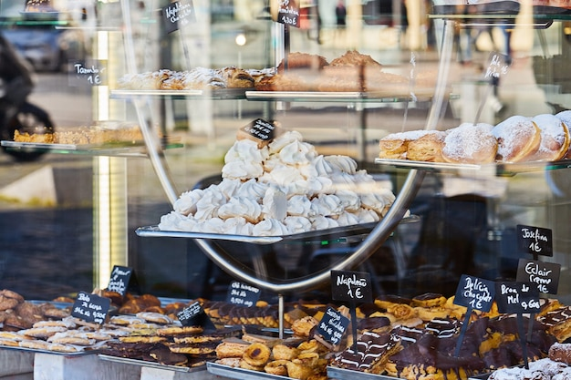 Витрина уютной пекарни с разнообразной выпечкой, печеньем и пирогами. надпись на португальском эклере, торт, шоколад