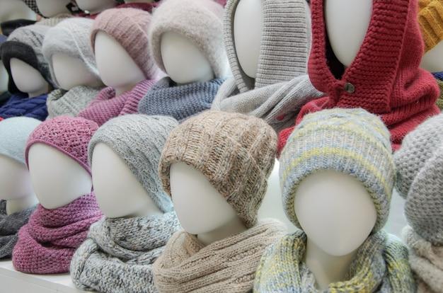 Витрина торговой палатки с разнообразием женских головных уборов для осенне-зимнего сезона.
