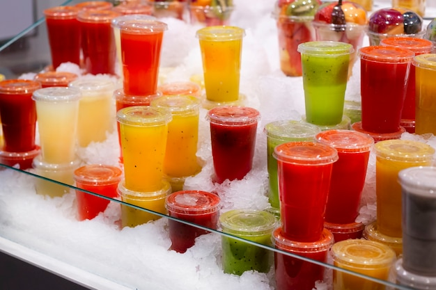 Showcase with different types of colorful cold juice and smoothie in the ice