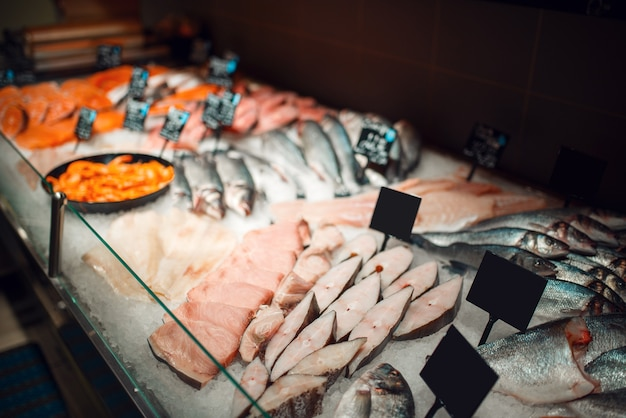 Showcase with fresh chilled fish in grocery store