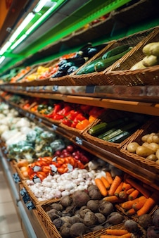Showcase with fresh fruits and vegetables in grocery store