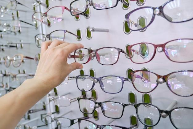 Витрина с очками в магазине, рука выбирая очки