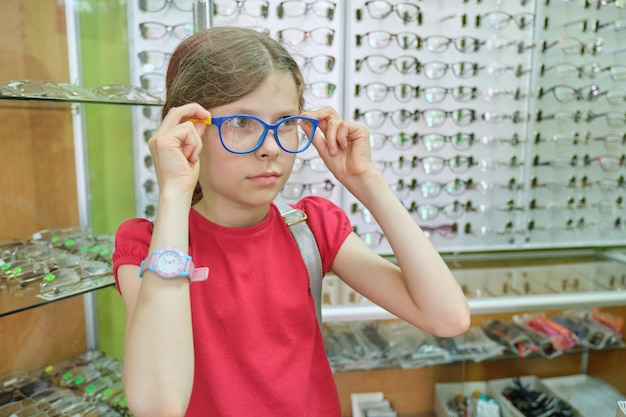 Showcase with glasses in optics store, child in glasses choosing a model of eyeglasses