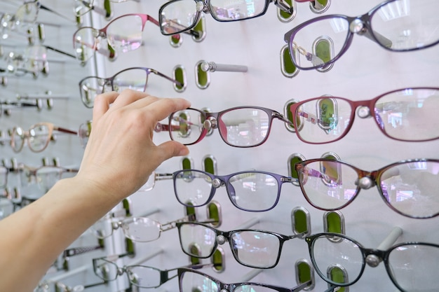 Showcase with glasses in the store, hand choosing glasses