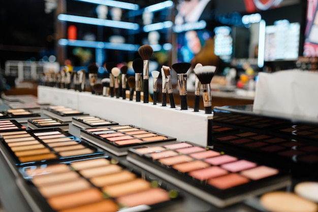 Showcase with powder and shadows in cosmetics store, nobody. luxury beauty shop, shelf with products in fashion market