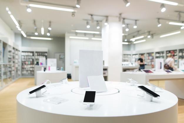現代の電気店でスマートフォンを展示します。テクノロジーストアの棚にある多くのスマートフォン。