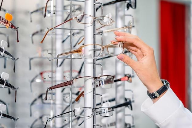 현대적인 안과 매장에서 안경을 진열하세요. 안경 손입니다. 확대.