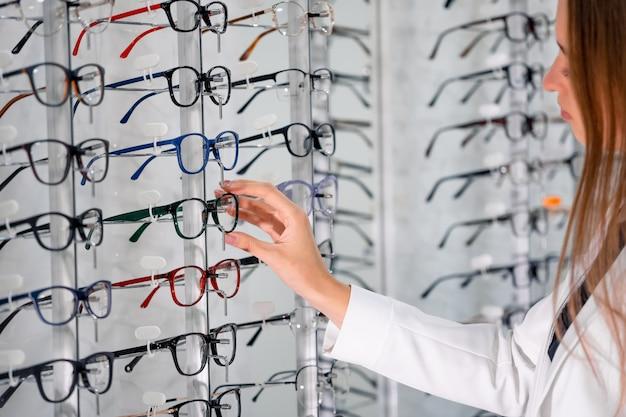 Витрина с очками в современном офтальмологическом магазине. руки женщины в очках. крупный план.