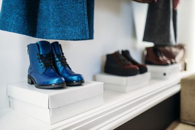 Showcase with stylish female shoes in clothing store