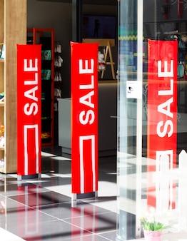 セールの看板が付いた赤いスタンドのある衣料品店のショーケース。割引の時間。