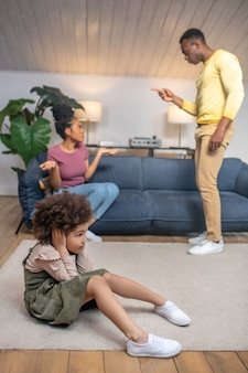 Showdown. dark skinned young parents having showdown and little daughter covering her ears with hands sitting on floor at home