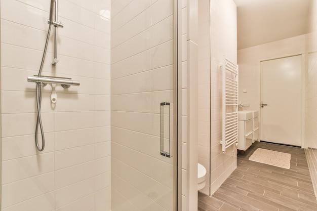 Душевая кабина со стеклянной дверью, расположенная внутри современной ванной комнаты с белыми стенами в квартире.