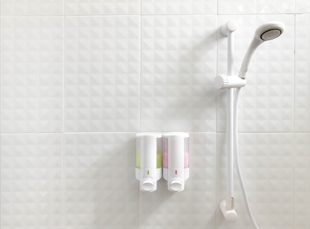 Shower head in bathroom with shower and shampoo bottle