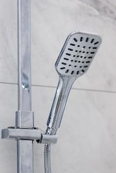 灰色のタイルの壁にシャワーヘッド。