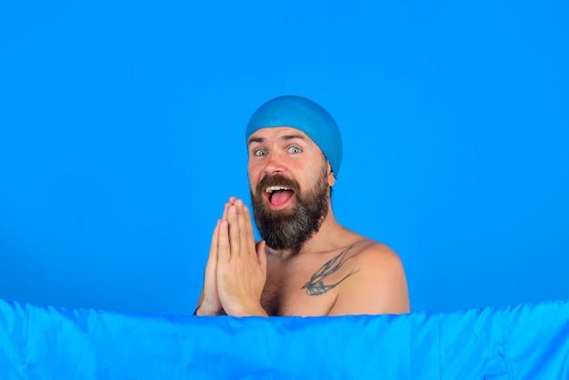샤워. 샤워하는 남자. 욕조. 헤어 케어. 바디워시. 수염 난 남자는 샤워를 합니다. 헤어 케어. 목욕 모자에 있는 남자.