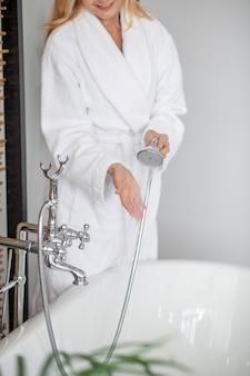 シャワー。手にシャワーと白いバスローブの女性