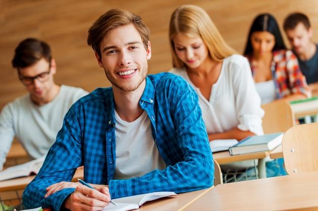 教育への献身を示しています。教室のフロントデスクに座ってメモ帳に書き込み、カメラを見ているハンサムな若い男