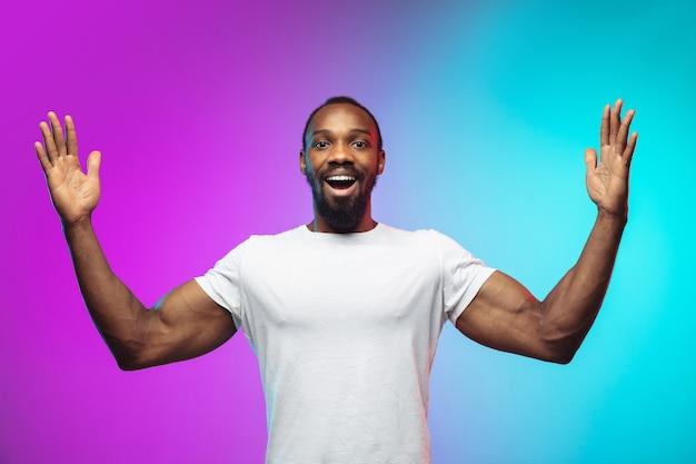 거대함을 보여주고 있습니다. 네온으로 그라데이션 스튜디오 배경에 아프리카계 미국인 젊은 남자의 초상화. 캐주얼 스타일의 아름다운 남성 모델, 흰색 셔츠. 인간의 감정, 표정, 판매, 광고의 개념.