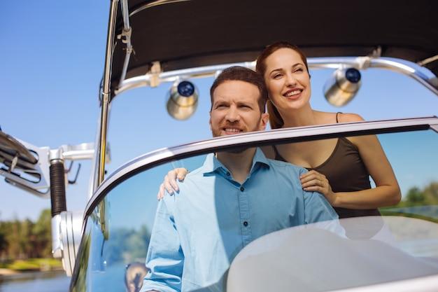 愛情を示しています。夫と一緒にボートを航海しながら、夫を抱きしめ、幸せそうに笑う元気な若い女性