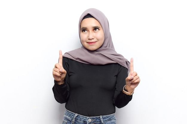 젊고 아름다운 이슬람 아시아 여성이 베일 히잡(veil hijab) 드레스를 입은 모습을 보여주고 가리키고 있다