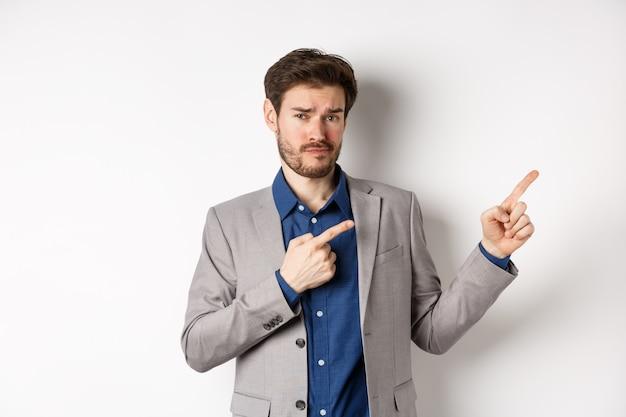 Показываю плохой пример. скептически настроенный бизнесмен недоволен и хмурится, указывая на баннер в правом верхнем углу, стоящий на белом фоне.