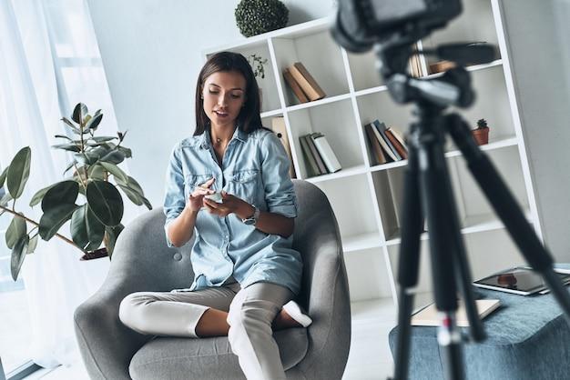 美容製品を表示しています。屋内で新しいビデオを作りながら新しい化粧品を適用する魅力的な若い女性