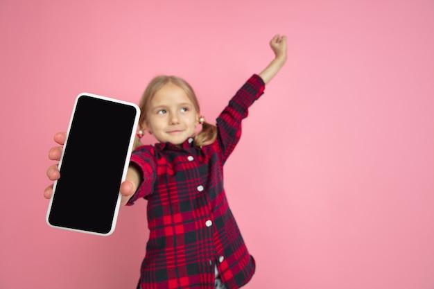 Отображается пустой экран. портрет кавказской маленькой девочки на розовой стене.