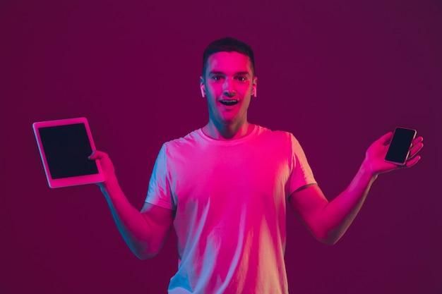 Отображается пустой экран. портрет кавказского человека, изолированные на розово-фиолетовой стене студии.