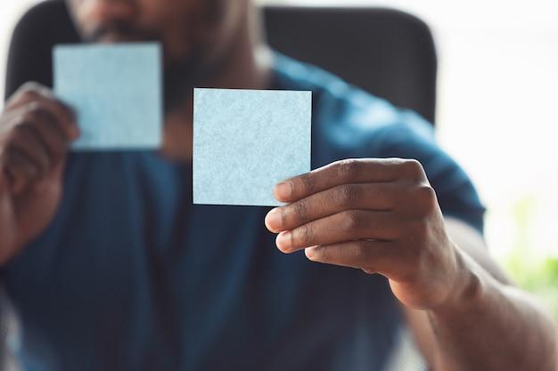 Mostra adesivi vuoti. primo piano delle mani maschili afro-americane, che lavorano in ufficio.
