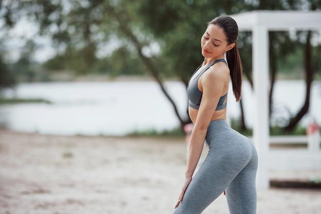 Показываю тело. брюнетка в спортивной одежде занимается фитнесом на пляже