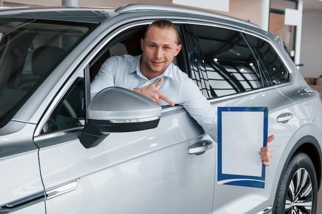 人差し指で表示しています。紙とドキュメントを手にしてモダンな白い車に座っているマネージャー