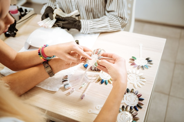 Showing color. cute stylish daughter wearing bright bracelets showing the best colors of shellac