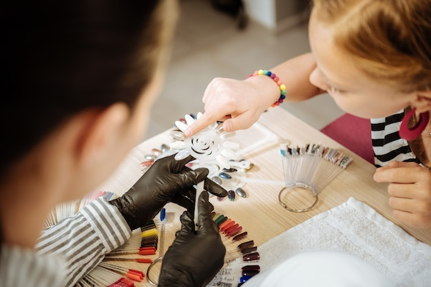 Showing color. cute teenage girl wearing pink earrings showing color for her nails while visiting beauty saloon