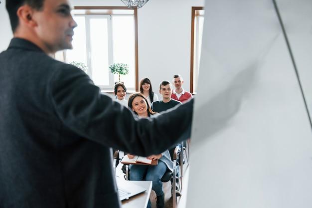 データを表示しています。昼間の近代的な教室でのビジネス会議での人々のグループ