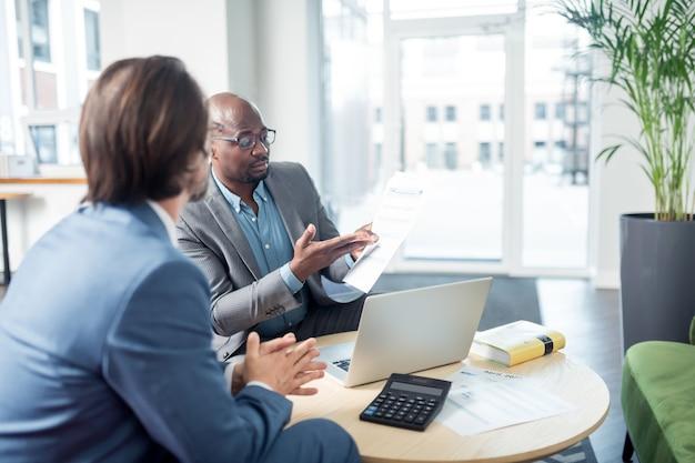 문서를 표시합니다. 회의 중 상사에게 문서를 보여주는 검은 피부의 자격을 갖춘 직원