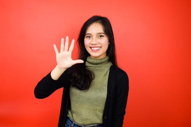 赤い孤立した背景と黒のセーターを使用して若い美しいアジアの女性の5本の指を示しています