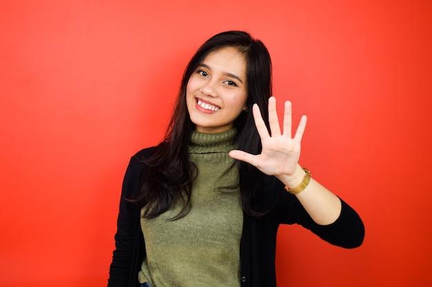 赤い孤立した背景と黒のセーターを使用して若い美しいアジアの女性の5本の指を示す