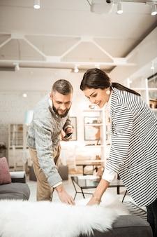 Показаны пушистые украшения. любопытная веселая пара осматривает кусок меха на пушистость и решает купить его