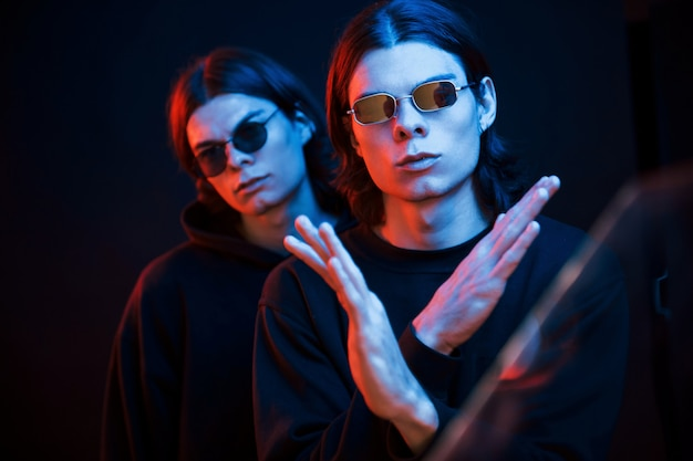 Showing gesture that means stop or don't. portrait of twin brothers. studio shot in dark studio with neon light