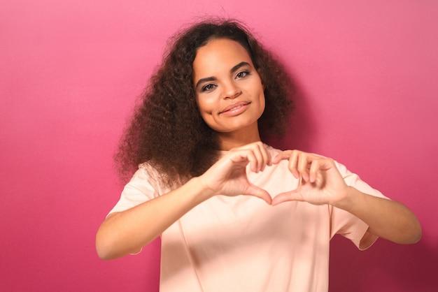 Показывая жест сердца или любви, красивая молодая женщина позитивно смотрит вперед в персиковой футболке, изолированной на розовой стене