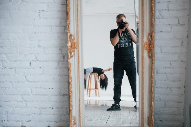 Sto mostrando ciao. uomo con la macchina fotografica che cattura un colpo nello specchio vintage. la ragazza si sta divertendo dietro