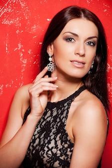 彼女の美しいイヤリングを見せています。赤い背景に立っている間彼女のイヤリングに触れる黒いドレスの美しい若い女性