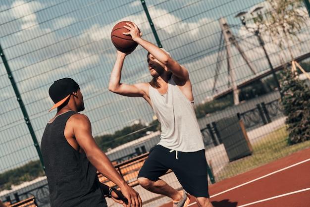 그의 최고의 샷을 보여줍니다. 야외에서 시간을 보내는 동안 농구를하는 스포츠 의류에 두 젊은 남자